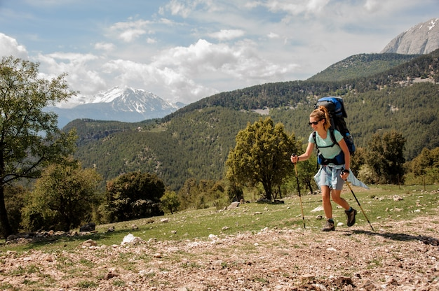 Female backpacker travels down the road in hills Premium Photo