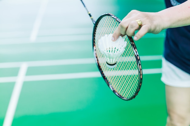 Female badminton single player hand hold white shuttle cock with racket Premium Photo