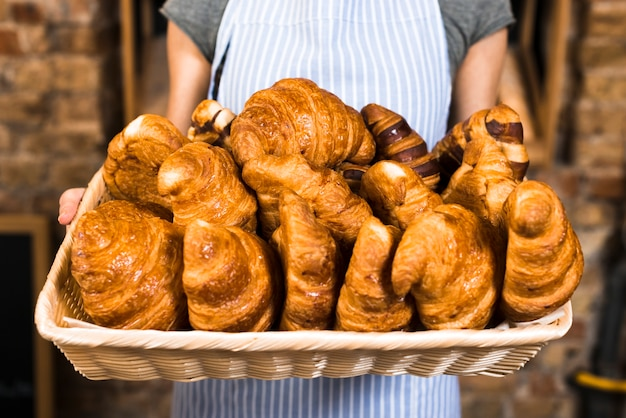 Female baker's hand holding basket of baked croissant Free Photo