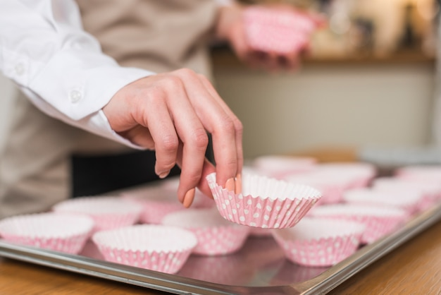 Female baker's hand placing the cupcake case on the tray Free Photo