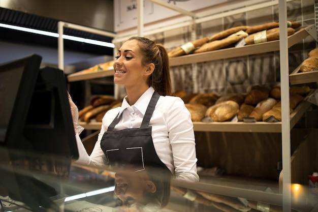 컴퓨터에서 작업하고 슈퍼마켓에서 빵을 판매하는 여성 베이커 판매자 무료 사진