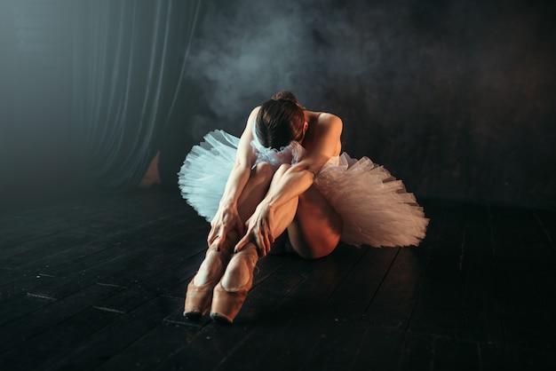 Артистка балета в белом платье сидит на полу, гибкость тела. тренировка балерины в танцевальном классе Premium Фотографии