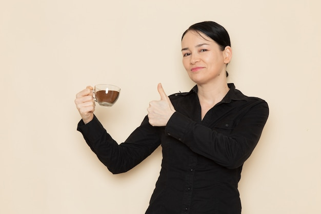 Female barista in black shirt trousers holding cup coffee on the white wall Free Photo