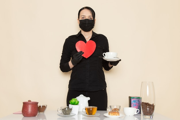 Female barista in black shirt trousers with coffee brown dried tea equipment ingredients in black sterile mask on the white wall Free Photo
