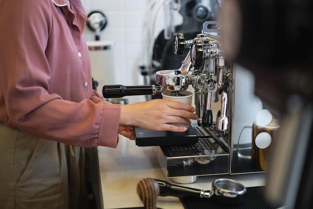 Female barista making coffee in a coffee machine Premium Photo