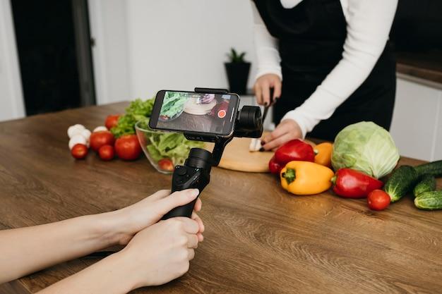 Blogger femminile che si registra mentre prepara il cibo Foto Gratuite