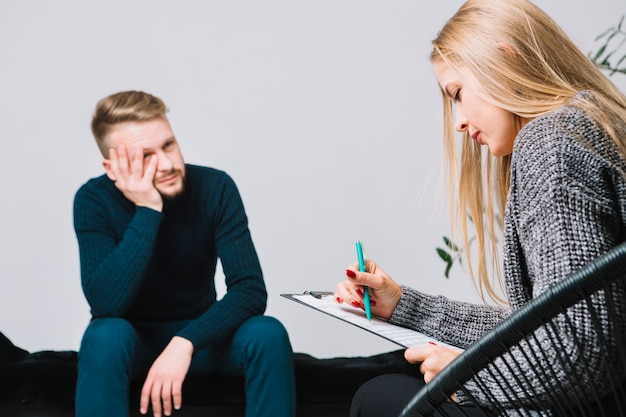 Female blonde young psychologist consulting a male client ...