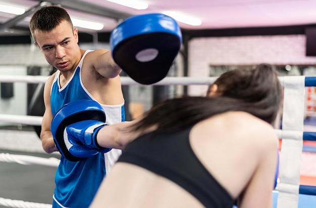 女性ボクサーがトレーナーと練習 無料写真