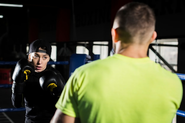 Female boxer training with male boxer in the ring Free Photo