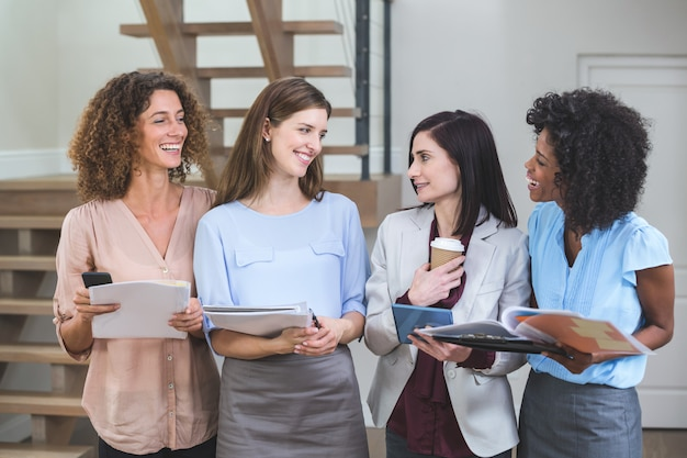 Female business colleagues standing together with file and digital tablet Premium Photo