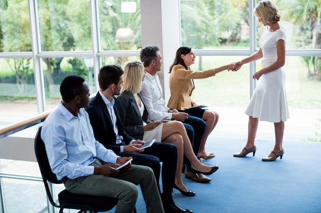 Female business executive shaking hands with a participant Premium Photo