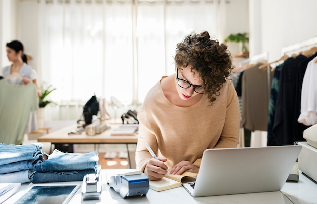 A female business owner is using the laptop Premium Photo