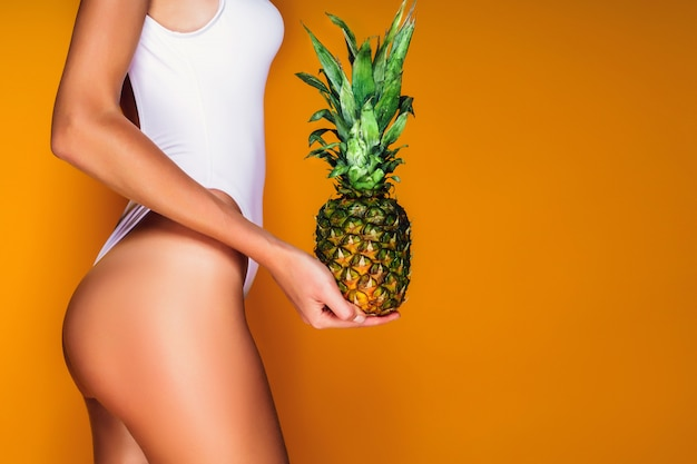 Female buttocks, sexy ass. young sporty woman holding a pineapple in her hand. Premium Photo