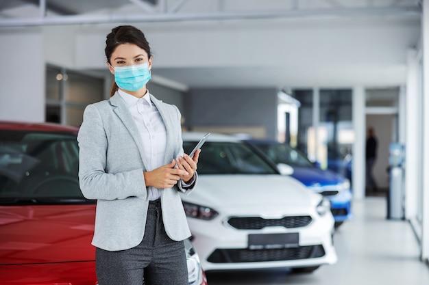 カーサロンに立ってコロナウイルスの発生時にタブレットを保持しているフェイスマスクとスーツを着た女性の自動車販売業者。 Premium写真