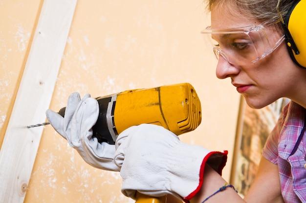 Female carpenter  at work using hand drilling machine Premium Photo