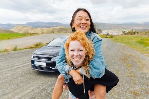 Female carrying girlfriend on back on roadside Free Photo