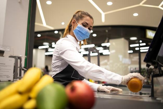 コロナウイルスのパンデミックのために危険な仕事をしている間、衛生的な保護マスクと手袋を着用しているスーパーマーケットの女性レジ係 無料写真