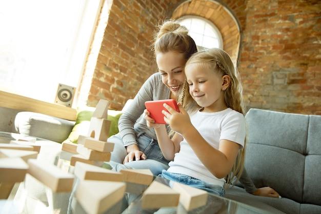 여성 백인 교사와 어린 소녀, 또는 엄마와 딸. 홈 스쿨링 무료 사진