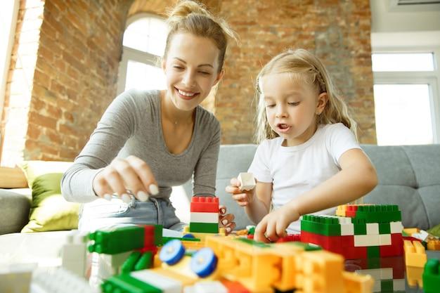 女性の白人教師と小さな女の子、またはママと娘。ホームスクーリング 無料写真