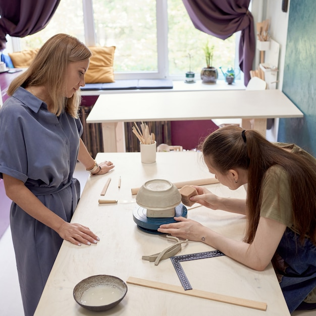 Мастер керамики и молодой ученик делают гончарные изделия в мастерской Premium Фотографии