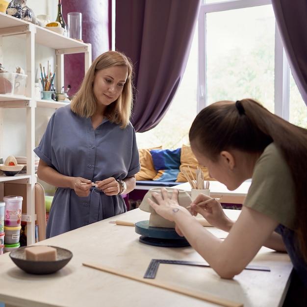 Учительница керамики смотрит на молодого ученика, занимающегося гончарным делом в мастерской Premium Фотографии