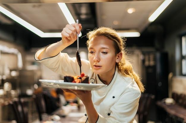 女性シェフが丁寧にソースを皿に注ぐ 無料写真