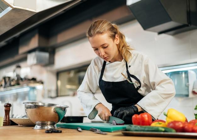 Cuoco unico femminile che taglia le verdure in cucina Foto Gratuite