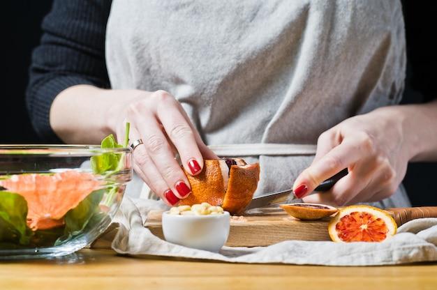 Female chef cuts red oranges for salad with arugula. Premium Photo