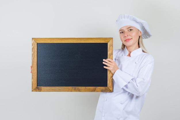 白い制服を着て黒板を持って陽気に見える女性シェフ。 無料写真