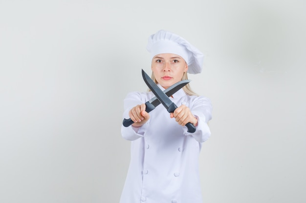白い制服を着た交差ナイフを保持し、真剣に見える女性シェフ 無料写真