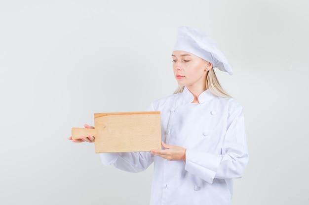 白い制服でまな板を保持している女性シェフ 無料写真