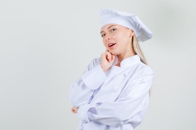 白い制服を着た頬に指を持って魅力的に見える女性シェフ。 無料写真