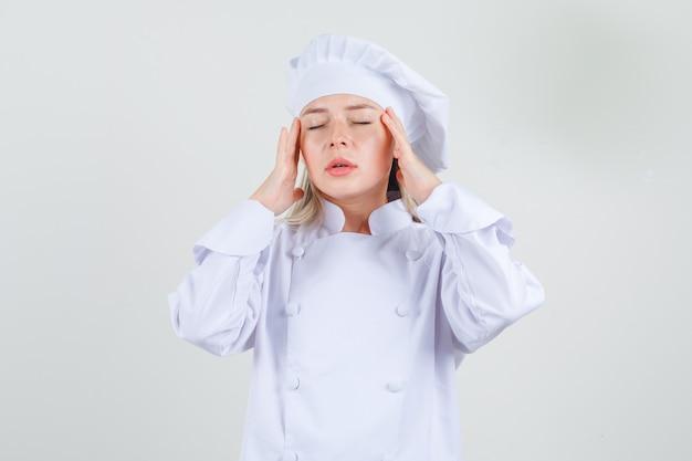 白い制服を着た寺院に指を持って疲れているように見える女性シェフ 無料写真