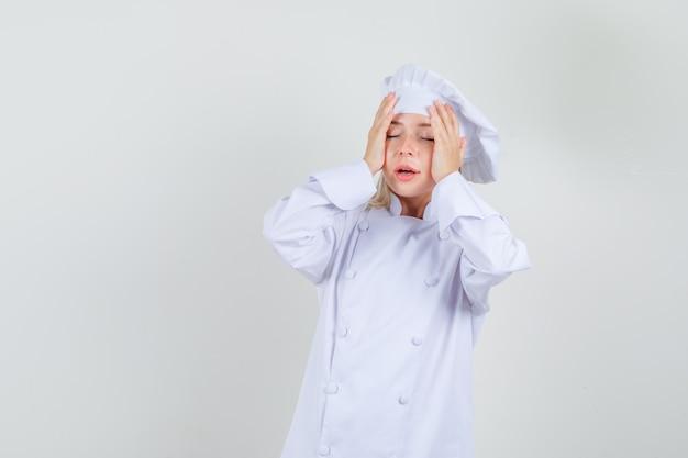 Cuoco unico femminile che tiene le mani alla testa in uniforme bianca e che sembra dispiaciuto. Foto Gratuite