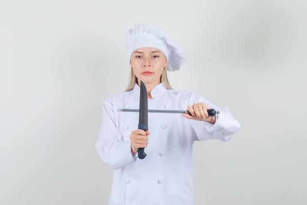 白い制服を着たナイフと鉛筆削りを保持し、真剣に見える女性シェフ 無料写真