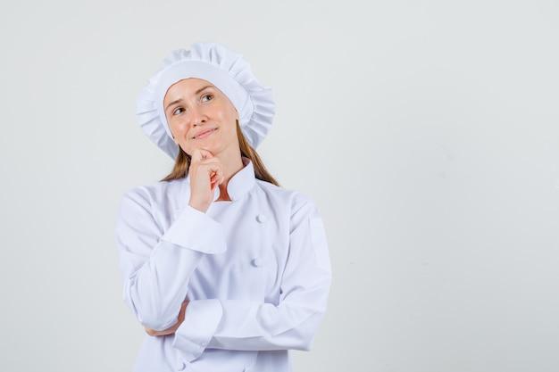 Cuoco unico femminile che osserva in su con la mano sul mento in uniforme bianca e che sembra promettente. vista frontale. Foto Gratuite
