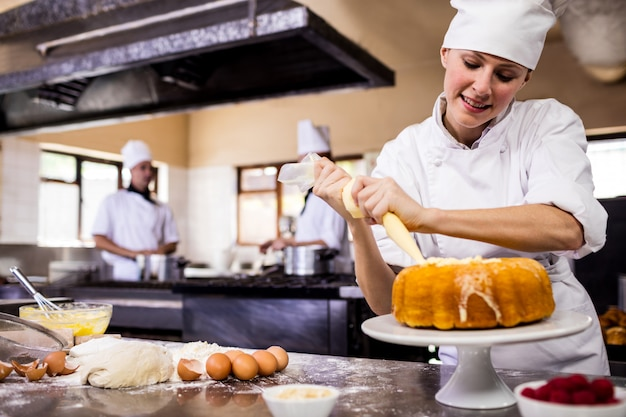 Female chef piping a cake in kitchen Premium Photo