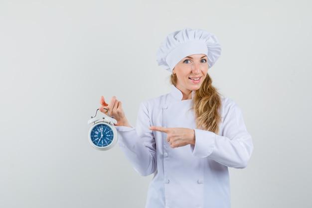 Cuoco unico femminile che indica alla sveglia in uniforme bianca e che sembra allegro Foto Gratuite