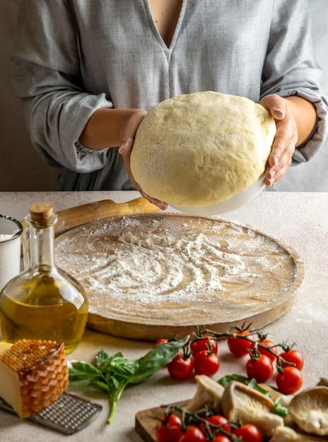 Женский повар готовит тесто для пиццы Бесплатные Фотографии