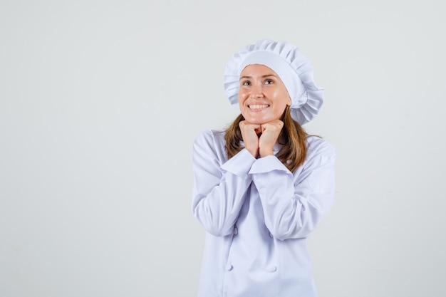 Cuoco unico femminile che sostiene il mento sui pugni in uniforme bianca e sembra speranzoso Foto Gratuite