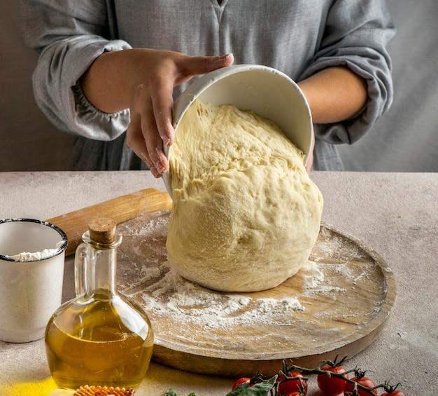 Женщина-повар кладет тесто для пиццы на деревянную доску Бесплатные Фотографии