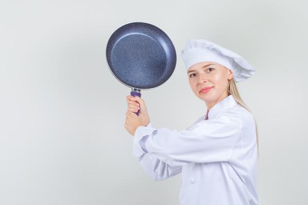 白い制服を着たフライパンで脅し、面白そうな女性シェフ 無料写真
