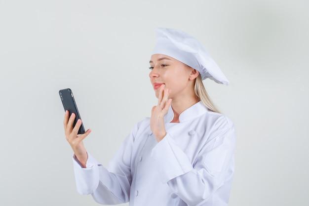 白い制服を着てビデオコールに手を振って、陽気に見える女性シェフ 無料写真