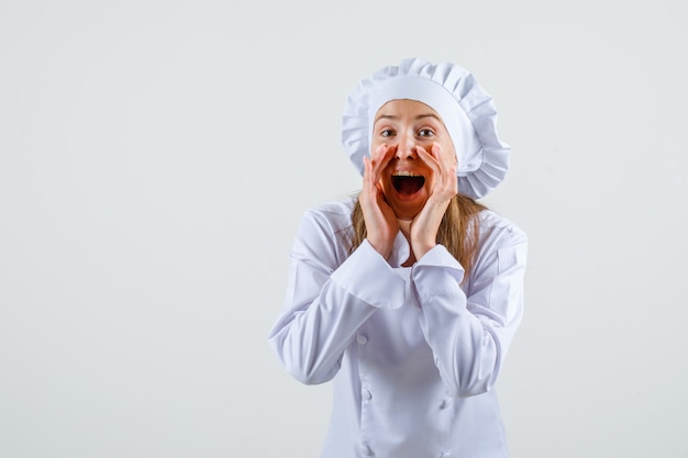 Female chef in white uniform telling something confidential and looking optimistic Free Photo