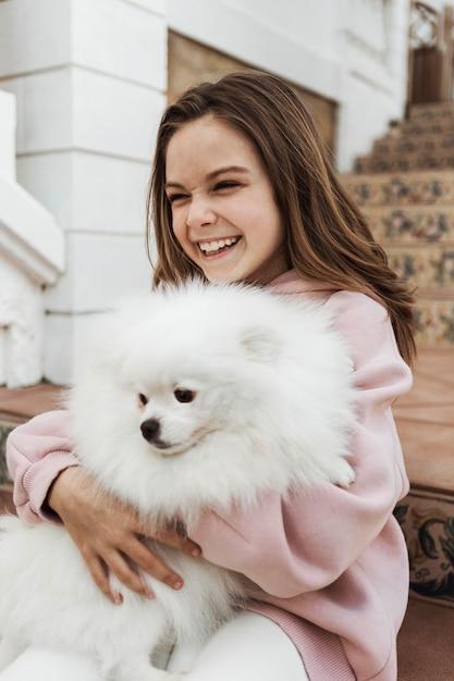 Female child hugging her fluffy dog Free Photo