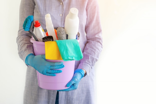 Female cleaner holding a bucket with cleaning supplies. Premium Photo
