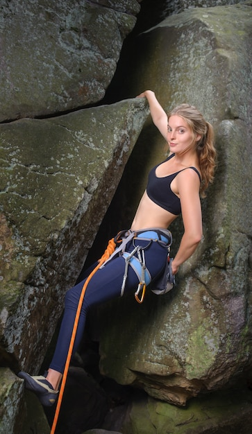 Female climber climbing with rope on a rocky wall Premium Photo