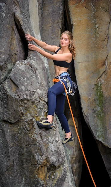 Female climber climbing with rope on a steep rocky wall Premium Photo