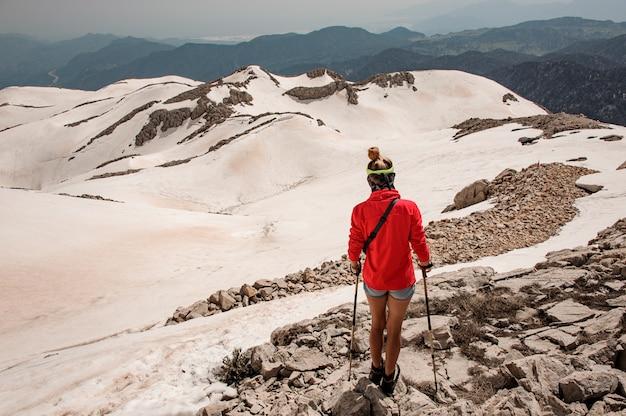 Female climber with walking sticks in mountains Premium Photo