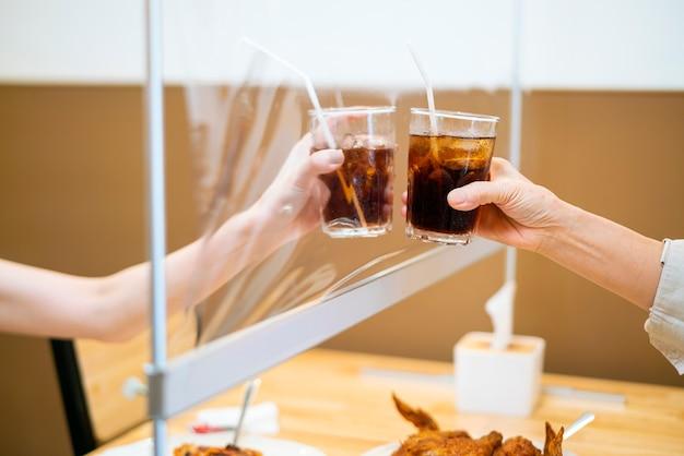 Женщина звонит в стакане воды со своей матерью, которая сидит за пластиковой перегородкой стола в ресторане Premium Фотографии